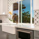 farmsink, gold faucet, white cabinets, gray cabinets, quartz countertops, white marble mosaic, marble backsplash, countertop kitchen window